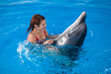 A cheerful red-haired woman in a red bathing suit bathes and holds the fins of a dolphin in a blue pool