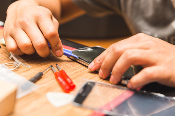 Man Removing Screen Glass from Broken Phone