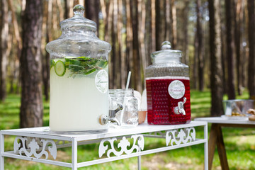 Glass jars with fresh lemonade and snacks on wooden tables. Wedding party bar in forest