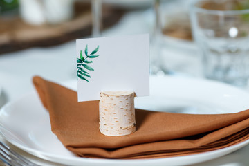 Wedding table setting with blank guest card on a dish. Rustic decor in brown tones