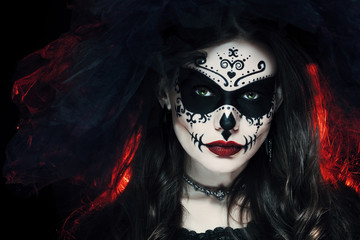 Close up studio portrait of beautiful woman with Halloween sugar skull makeup in red and black colors, wearing bridal veil. Model looking at camera. Dark, dead bride.