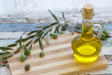 Olive oil in glass and olive on cutting board