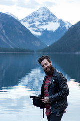 Stylish tattoed Hipster Man enjoys scenic mountain lake in Austria