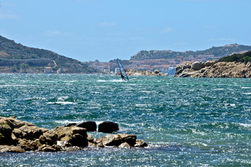 Caprera seascape with a man windsurfing and the view of La Maddalena city in the background