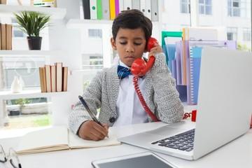 Businessman writing on book while talking on landline phone