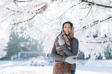 A portrait of a girl with a beautiful smile in the winter, snowly and sunny day on the outdoors.