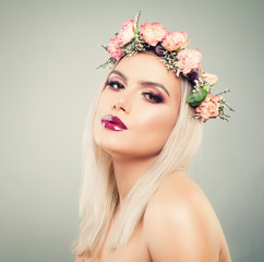 Beautiful Woman with Flowers in her Hair. Healthy Model with Makeup and Blonde Hairstyle