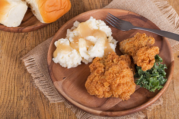 Fried Chicken and Mashed Potato Dinner on a Wooden Plate