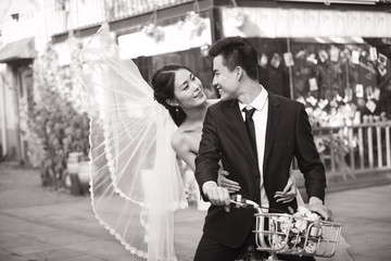 romantic asian newly-wed riding a bicycle, black and white