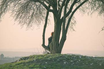 The old woman sitting on the tree looking at the Cracow panorama. Soft vintage colors. Hipster photo. Nostalgia and adventure