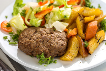 Tasty beef cutlet with salad and potato wedges