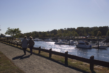 two people walking on a path with boats in the background