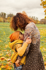 Happy Autumn Family. Cute Mother and Son  Hugging in Fall Park Outdoors