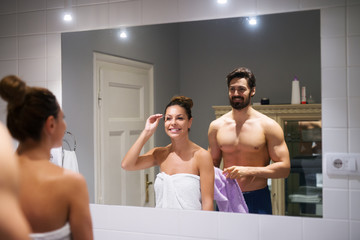 Young cute girl plucking eyebrows depilating with tweezers in front of a strong muscular shirtless man whole holding towel in the bathroom.