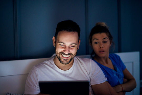 Handsome happy man sitting on the bed and looking on a tablet while his curious wife peeking behind him.