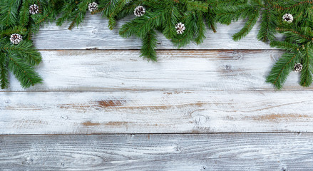 Top border of Christmas fir branches and pine cones on rustic white wooden background