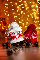 Knitted hats with deer./Knitted hats with deer on the background of New Year's lights garlands. New Year's celebration.