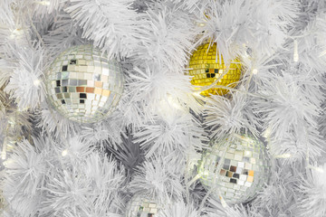 Glass Christmas ball ornaments with lights on white branches. Spherical decorations are used to festoon a tree.