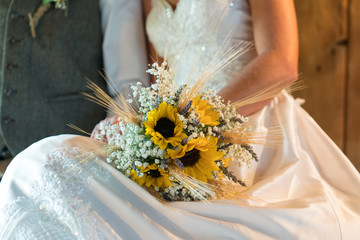 bride holding fresh flower bouquet in dress