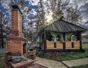 landscape of sunny day with wooden gazebo and outdoor brick oven in backyard