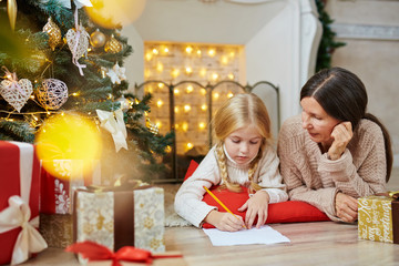 Cute little girl writing letter to Santa on xmas night with her grandmother near by