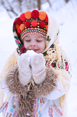 little girl in winter forest dressed in the Ukrainian national clothes.