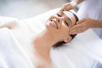 Young smiling woman enjoying facial spa massage in beauty salon