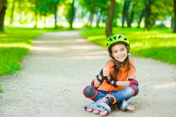 Happy girl in a protective helmet and protective pads for roller skating sitting on the road and showing thumbs up. Space for text