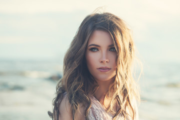 Attractive Model with Perfect Makeup and Wavy Colored Hair Outdoors. Young Woman Walking on the Coastline