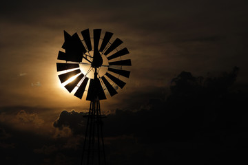 A windmill against a setting sun and storm clouds.