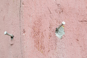 Nail on old pink wall