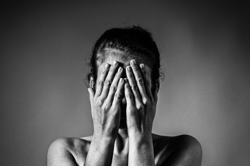 Wall Mural - Concept of fear, shame, domestic violence. Woman covers her face her hands on light  scratched background. Black and white image.