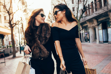 Women with shopping bags walking along the city street