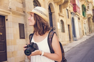 Young woman tourist with camera sightseeing in Valletta, Malta