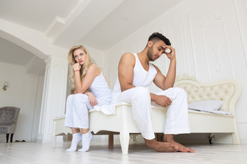 Young Couple Sitting Separate On Bed, Having Conflict Relationships Problem, Sad Negative Emotions Hispanic Man And Woman Lovers Argue In Bedroom