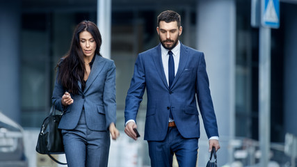 Business Woman and Business Man in Tailored Suits Walk on the Busy Big City Street.