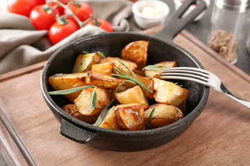 Delicious baked potatoes with rosemary in pan on table