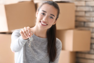 Happy young woman holding keys from her new apartment