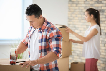 Young couple packing boxes at home while preparing for house move