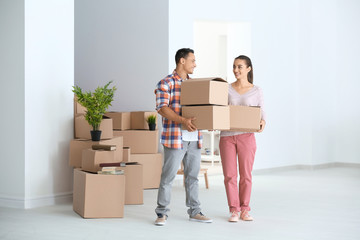 Happy young couple with moving boxes in their new apartment