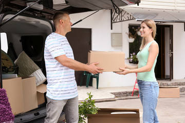 Happy couple with moving box near car outdoors