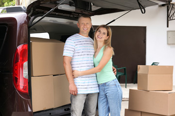 Happy couple with moving boxes near car outdoors