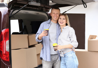 Happy couple with coffee and moving boxes near car