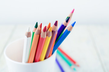 Color pencils in cup on light background, closeup