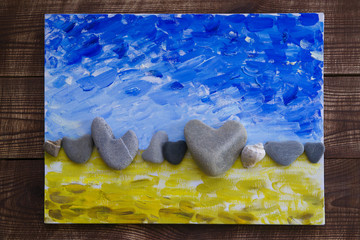 Abstract handmade picture with stones in the form of hearts on background