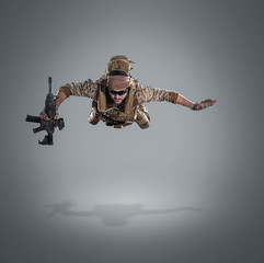 USA Army soldier with gun (motion effect).  Shot in studio on gray background. Action concept