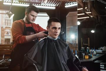 cutting process/ Barber cutting in barbershop. Hair clipper in hands