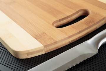 Kitchen cutting board and knife on a table