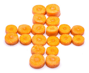 Group of sliced round orange carrot circles in the shape of cross like red cross emblem isolated on white background