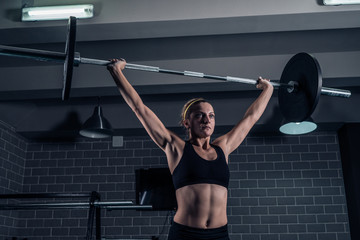 Athletic woman lifting a weight training at the gym. CrossFit